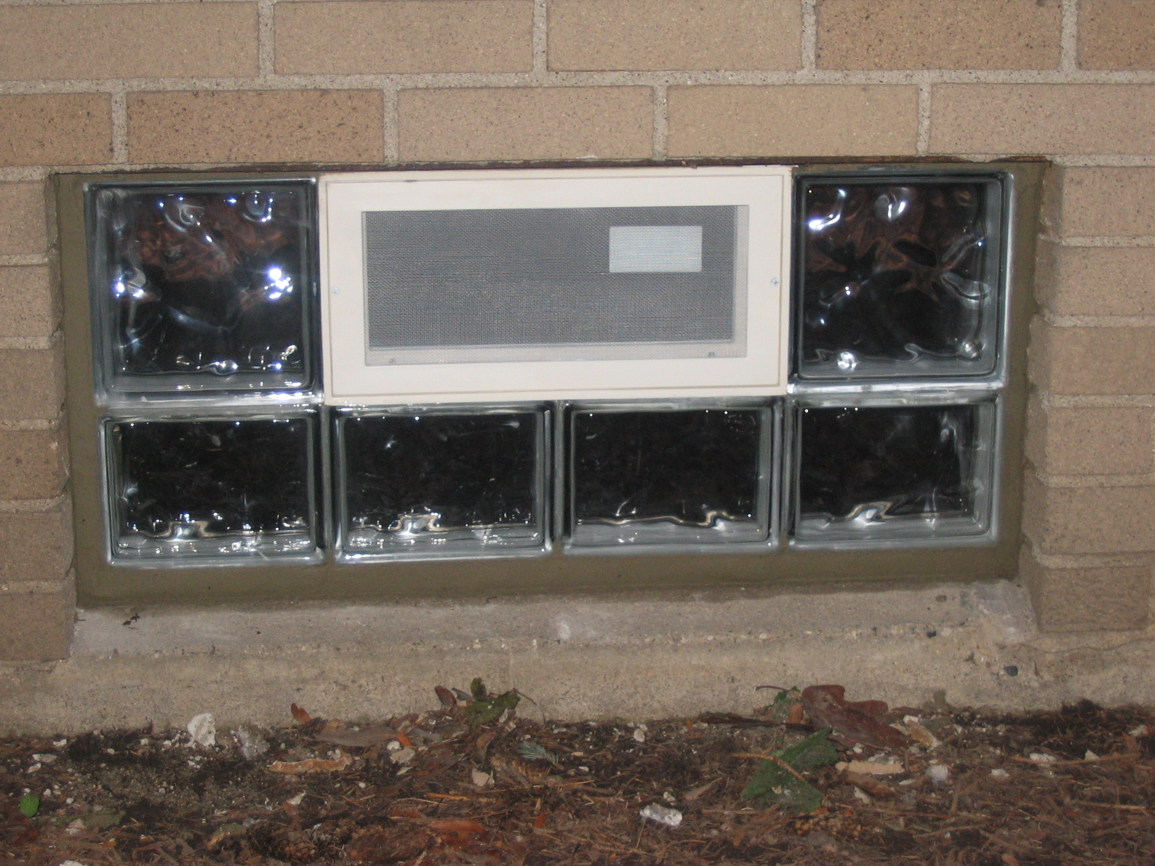 basement window with thick glass and fine metal screen