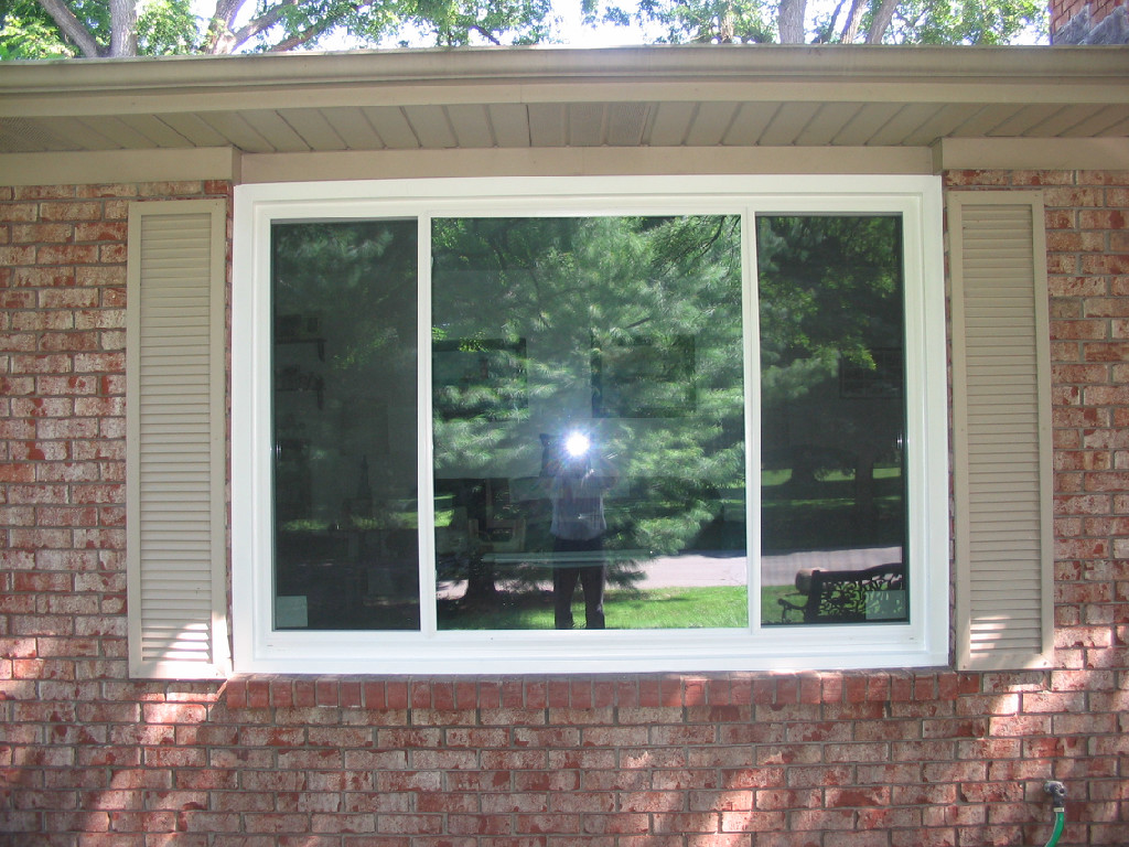 Window with white siding in a brick wall